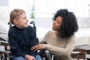 Child in wheelchair and therapist